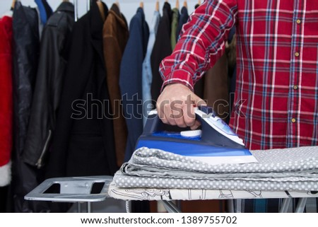 Man irons clothes on ironing board with blue iron. Housework and household concept #1389755702