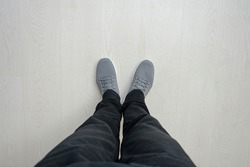 Man is about to take a step, wooden floor, feet in sneakers, close up, top view, copy space