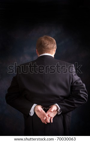 Man is arrested and handcuffed behind his back for white collar crime.