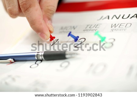 Man is attaching allpin on the calendar in hand. Picture of pen on the calendar.