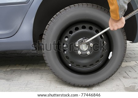 Man is changing winter tire with wheel wrench.