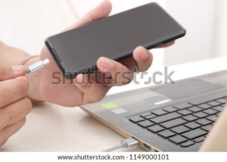 Man is connecting laptop to phone.
