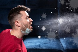 man is coughing. Influenza, cold, coronavirus. Infection through an airborne droplet. A guy in a red sweater and a medical mask is coughing. Visible coronavirus particles in the air.