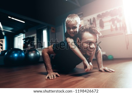 Man Is Doing Push Ups In Gym With Son On A Back. Parenthood Relationship. Sporty Family Concept. Active Lifestyle. Triceps Exercise. Holiday Leisure. Working Out Together. Fitness Day.