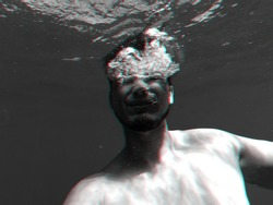 man is drowning in a deep blue sea under the water with an expression of horror and fear on her face. Black and white photo with 3D glitch effect