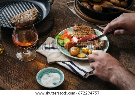 Man is eating dinner at a wooden table. Grilled steak with potatoes and salad