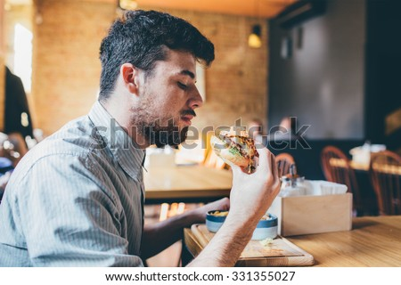 Man is eating in a restaurant and enjoying delicious food  #331355027