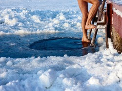 Man is going to swim in the ice hole at sunny day