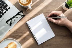Man is going to write something on blank notebook page on wood office desk table with cookies, cup of coffee and supplies. Morning life at work concept, top view.