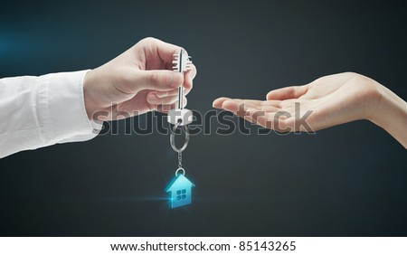 Man is handing a house key to a woman.Key with a key chain in the shape of the house. On a black background