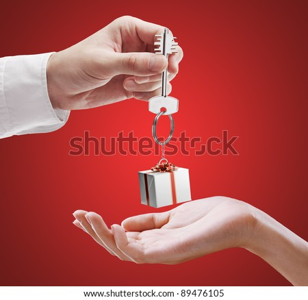 Man is handing a house key to a woman. Key with a keychain in the shape of the gift box. House key on a red background.