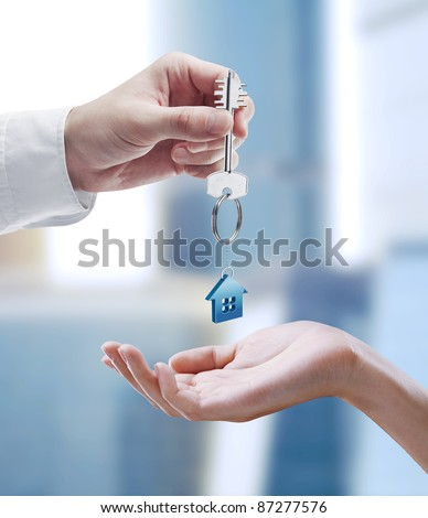 Man is handing a house key to a woman.Key with a keychain in the shape of the house.