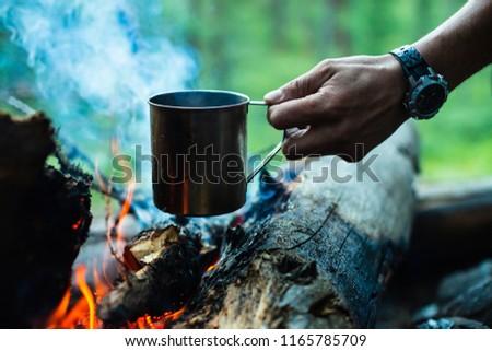 Man is heating tea in metal mug on bonfire. Hot drink on nature. Tea drinking in open air. Steel mug in human hand. Camping in dusk. Romantic warm atmosphere outdoor in twilight . Active rest. #1165785709