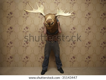 man is hiding behinde a moose head
