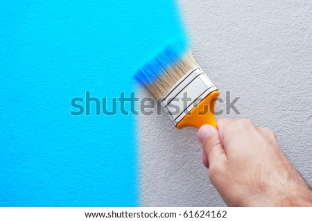 Man is holding a brush and painting a white wall