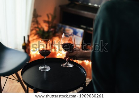 Man is holding a glass of wine. A glass of red wine is on a black table. Cosy romantic evening at home Stock fotó ©