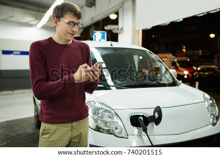Man is holding a phone. His electric car charged at the charging station #740201515