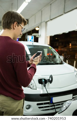Man is holding a phone. His electric car charged at the charging station #740201953