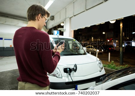 Man is holding a phone. His electric car charged at the charging station #740202037