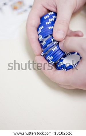 man is holding a set of blue gambling chips in his hands waiting to make his bet with cards blurred in the background