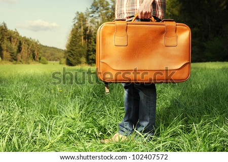 man is holding a travel suitcase