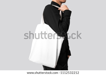 Man is holding bag canvas fabric for mockup blank template isolated on gray background.