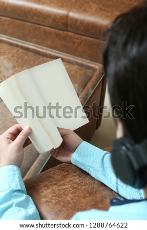 Man is holding book in hand and listening music with headphone.
