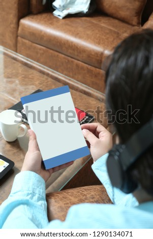 Man is holding closed book in hand and listening music with headphone.