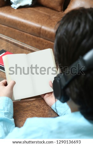 Man is holding open book in hand and listening music with headphone.
