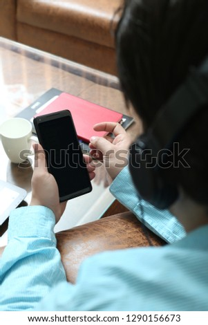 Man is holding smartphone in hand and listening music with headphone.