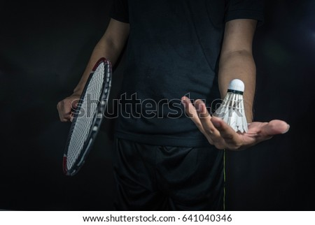 Man is holding the shuttlecock and the badminton racket. In dark background