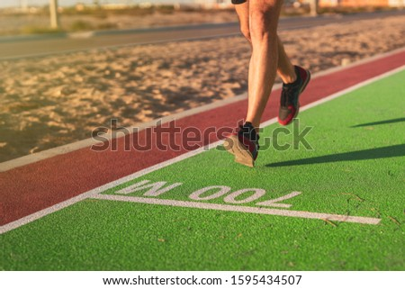 Man is jogging around the public park in the rubber flooring with markings