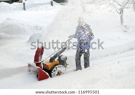 Man is making a path by removing snow with snow blower after winter storm.