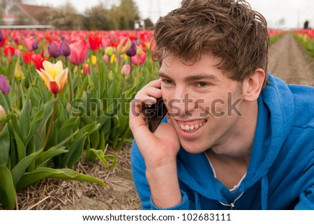 Man is making a positive phone call in the flower fields