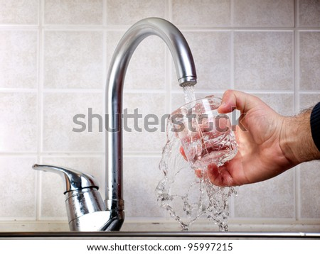 Man is pouring potable water from the faucet in a glass.