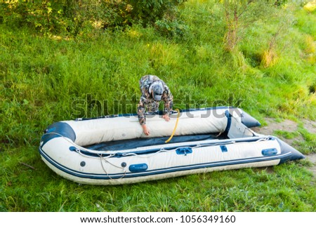 Man is preparing for fishing, inflatable rubber boat pump. #1056349160