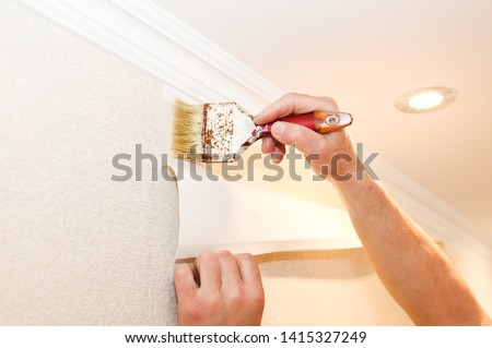 Man is putting glue on the wall with brush. Wallpaper hanging. Maintenance repair works renovation in the flat. Restoration indoors. Stockfoto ©