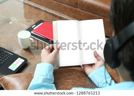 Man is reading book and listening music with headphone.
