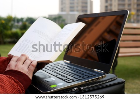 Man is reading book with laptop and bag.