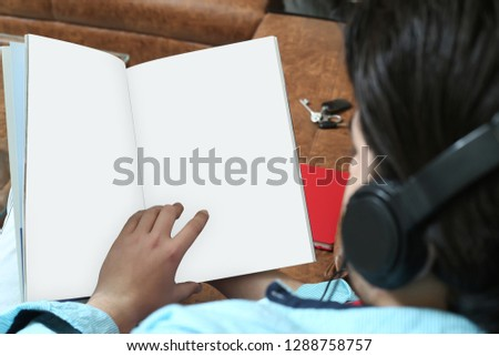 Man is reading magazine and listening music with headphone.