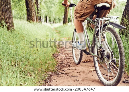 Man is riding bicycle on path in summer park, face is not visible