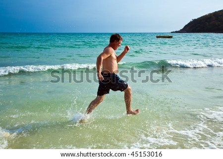 man is running along the beautiful beach, enjoying the water