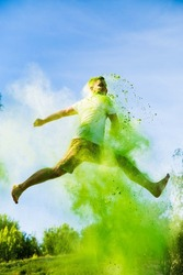 Man is running in the air. Green paints holi. bounce