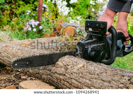 Man is sawing a wooden log with an electric chain saw #1094268941