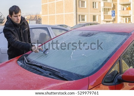 Man is scraping ice from frozen windshield window of car in winter. #529979761