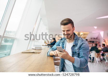 Man is sitting in front of the table near window. He is looking at cellphone and chatting with friends. Smiling young student has coffee break