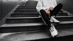 man is sitting on the stairs. Lifestyle photography. Urban wallpaper. Interior poster. Look book. Hype sneakers. Best