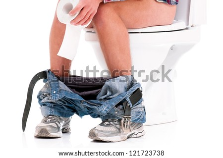 Man is sitting on the toilet bowl, holding paper in hands, on white background