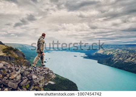 Man is standing on cliff, looking sky with clouds, against backdrop of lake and mountains. Concept travel, fishing, tourism in Russia #1007454742
