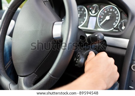 Man is starting his car; he is turning the ignition key under the wheel